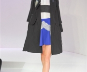 Carven Spring 2012 in black coat, white shirt, and blue skirt