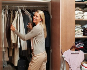 Portrait of a happy mature female making choices in wardrobe